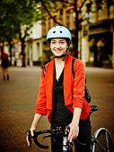 Smiling businesswoman with bike on sidewalk