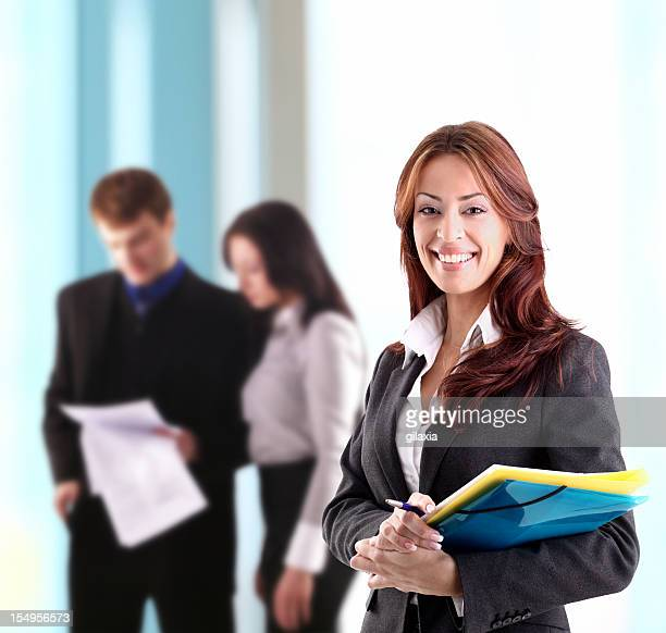Smiling businesswoman with colleagues in background.