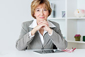 Portrait of charming businesswoman sitting at the desk in the office.