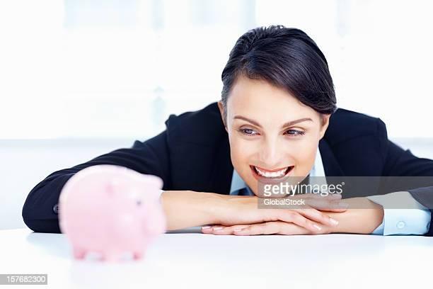 Sorridente donna d'affari con un Salvadanaio a porcellino
