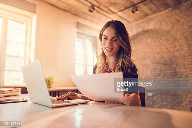 Smiling businesswoman working on paperwork and laptop in the office.