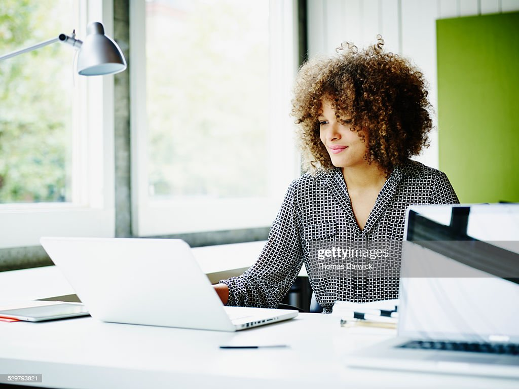 Smiling businesswoman working on project on laptop : Stock Photo