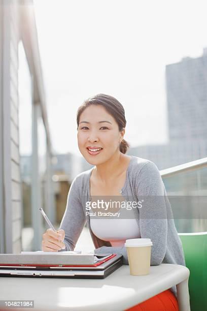 Lächelnd Geschäftsfrau Arbeiten auf urban Balkon
