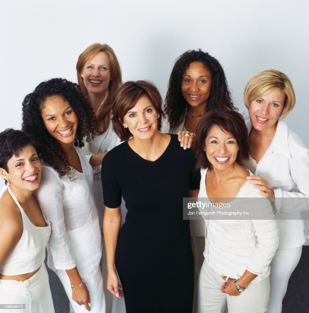 Smiling businesswomen dressed in white one in black : Stock Photo