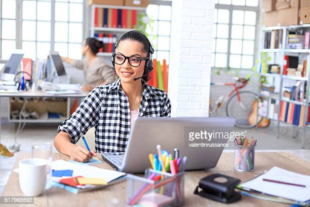 Operador de centro de llamadas sonriente en el trabajo