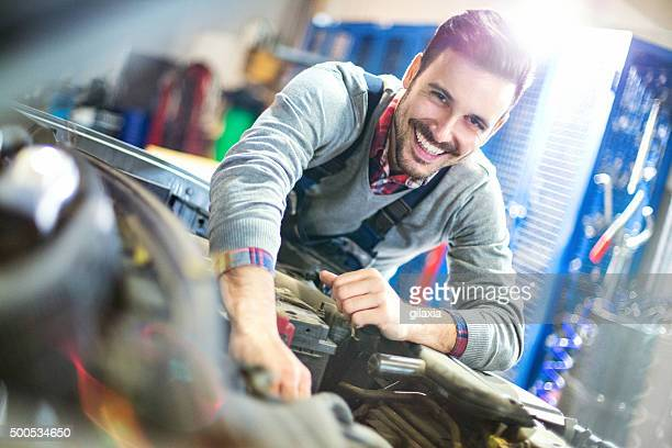 Smiling car mechanic dealing with an engine.