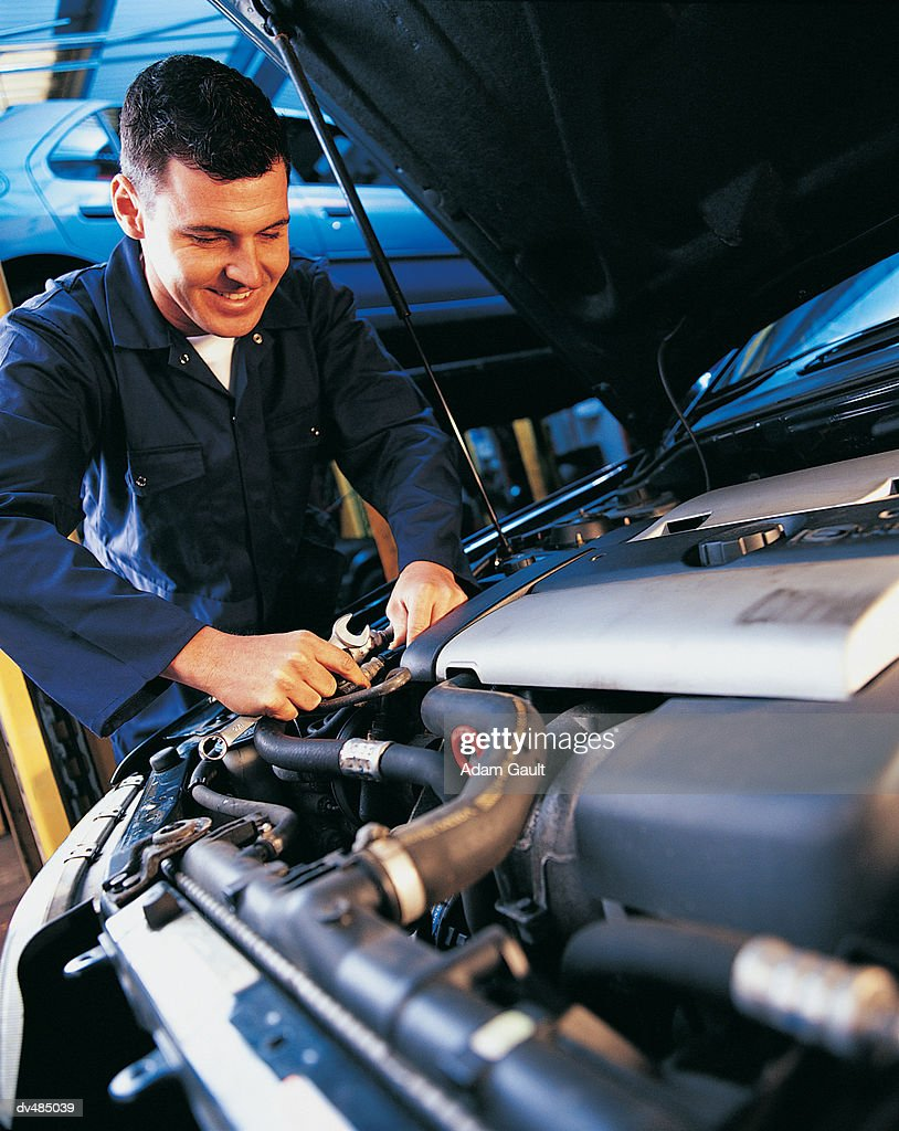 Smiling Car Mechanic Working On Car Engine : Stock Photo