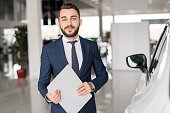 Waist up portrait of handsome car salesman looking at camera  and smiling holding clipboard standing in luxury dealership showroom