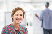 Smiling casual businesswoman in front of colleague in the office