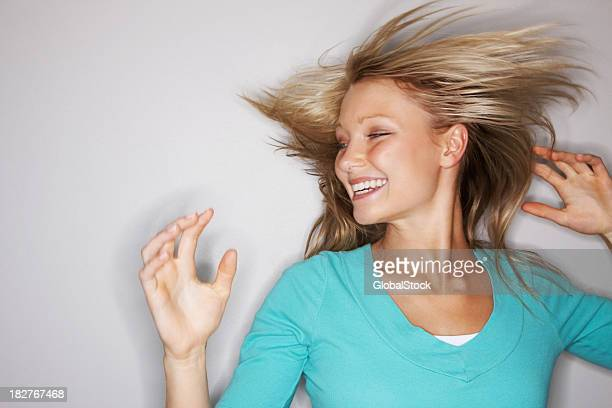 Smiling casual woman tossing her hair