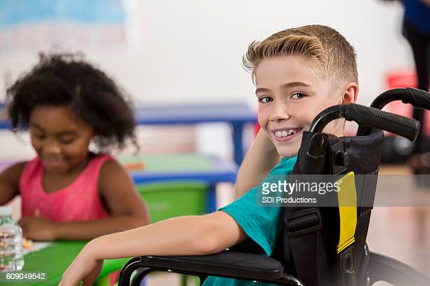 Smiling Caucasian boy in a wheelchair at school