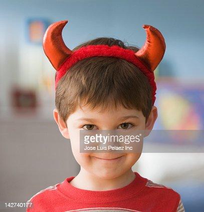 Smiling Caucasian boy in devil costume