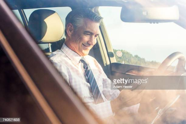 Smiling Caucasian businessman sitting in car texting on cell phone