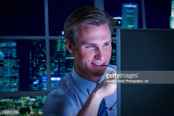 Smiling Caucasian businessman using computer