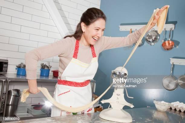 Smiling Caucasian chef making pasta in kitchen