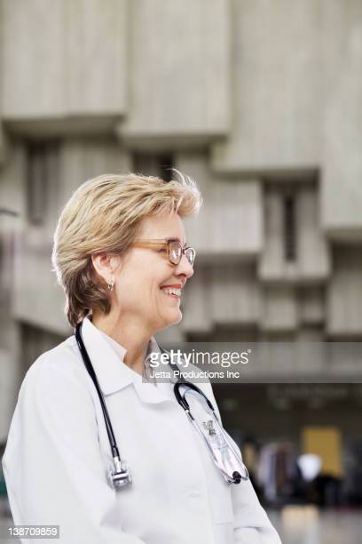 Smiling Caucasian doctor standing outdoors