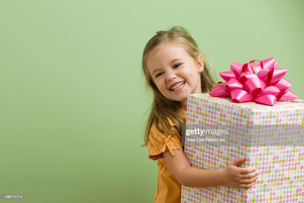 Smiling Caucasian girl holding birthday gift : Stock Photo