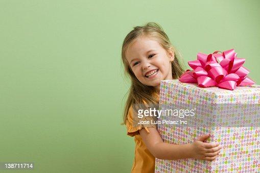 Smiling Caucasian girl holding birthday gift : Stockfoto