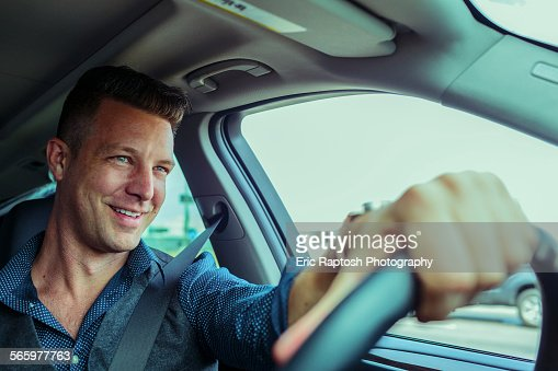 Smiling Caucasian man driving car