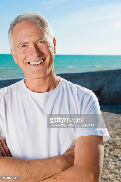 Smiling Caucasian man standing on beach