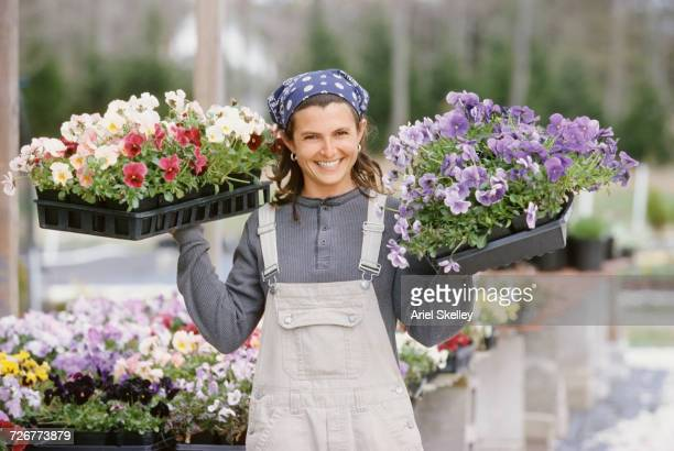 Smiling Caucasian woman carrying trays of flowers in nursery