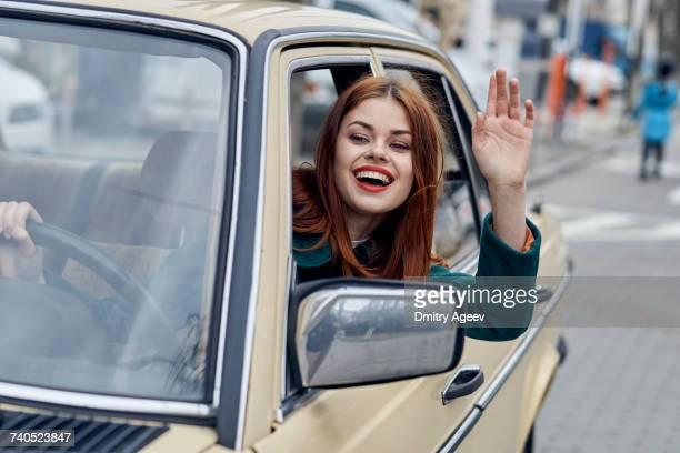 Smiling Caucasian woman driving car and waving