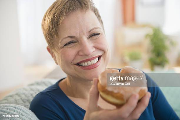 Smiling Caucasian woman eating donut