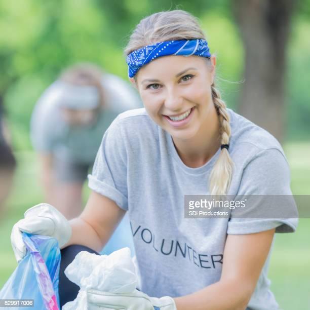 Femme de race blanche souriante aide les voisins nettoyer leur parc