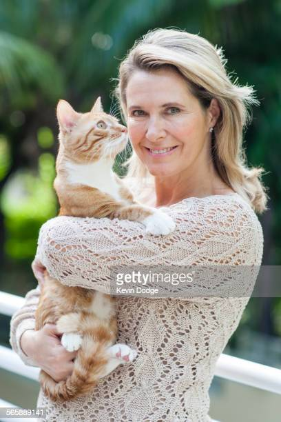 Smiling Caucasian woman holding cat outdoors