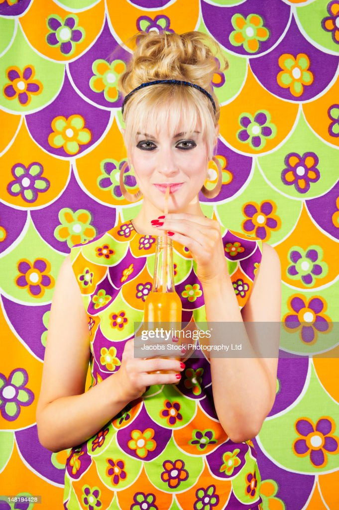 Smiling Caucasian woman in nostalgic dress drinking soda