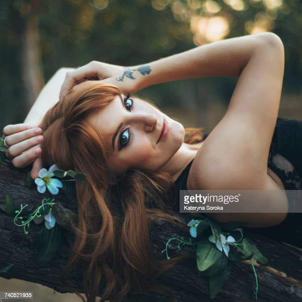 Smiling Caucasian woman laying on tree branch
