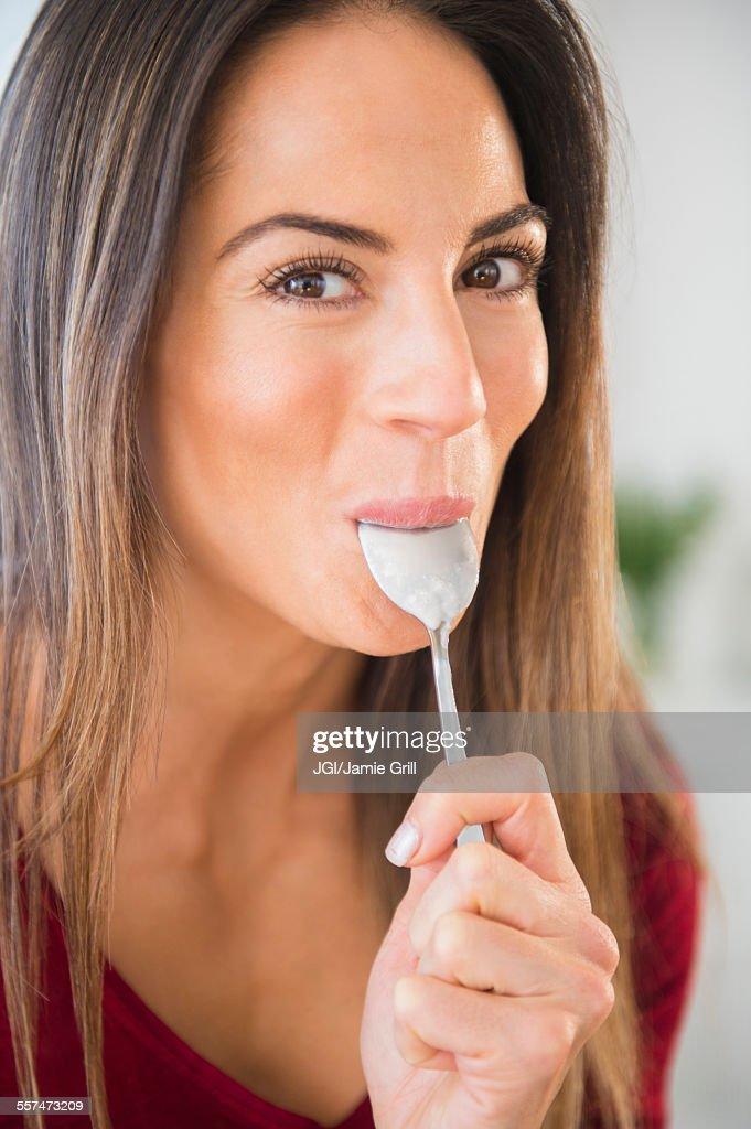 Smiling Caucasian woman licking spoon : Stock-Foto