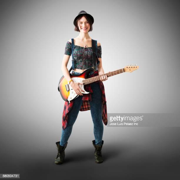 Smiling Caucasian woman playing guitar