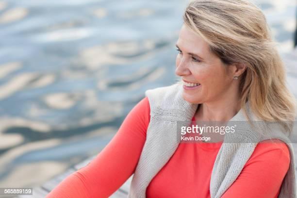 Smiling Caucasian woman rowing canoe on lake