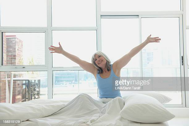 Smiling Caucasian woman sitting in bed