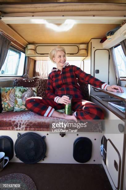 Smiling Caucasian woman sitting in camper van