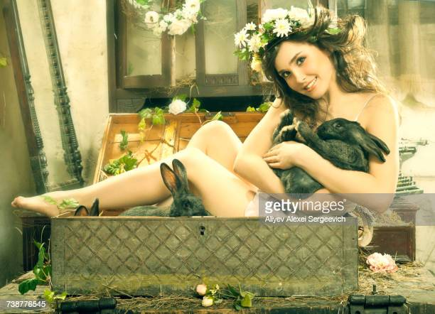 Smiling Caucasian woman sitting in trunk holding rabbit