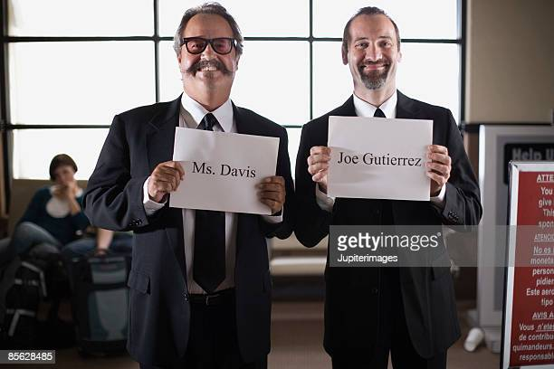 Smiling chauffeurs holding English signs in airport