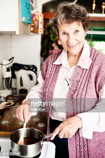 Smiling cheerfully, 80-plus woman cooks, still active and independent