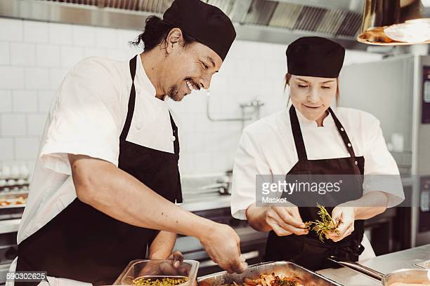 Smiling chefs garnishing dish in kitchen