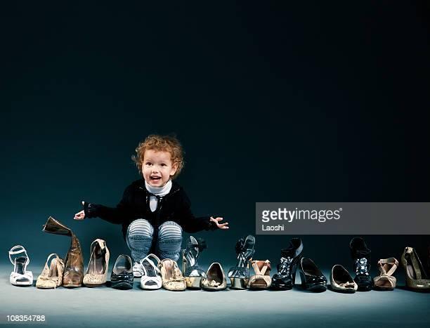 Smiling child choosing from a row of adult shoes