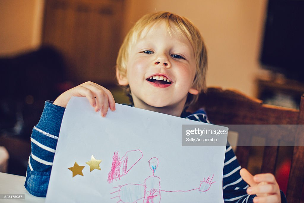 Smiling child holding up a picture he has drawn