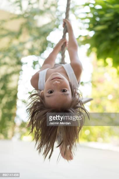 Smiling child swinging on rope at playground