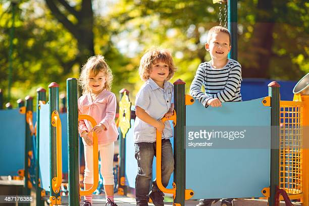 Smiling children enjoying in the park at playground.