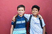 Best children friends standing with hand on shoulder against red background. Happy smiling classmates standing together on red wall after school. Portrait of multiethnic schoolboys enjoying friendship