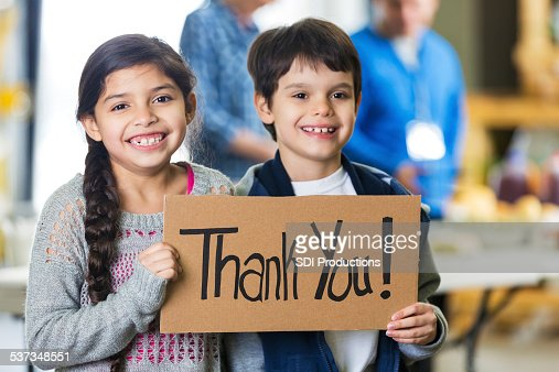Smiling children holding a thank you sign out of food bank.