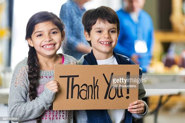 Adorável Hispânico crianças segurando sinal de agradecimento pelo Banco alimentar