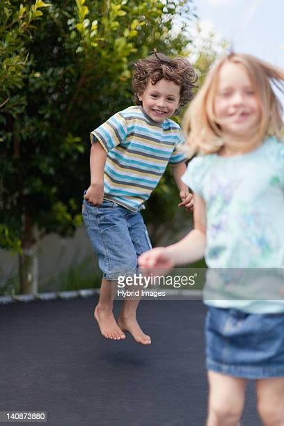 Smiling children jumping on trampoline