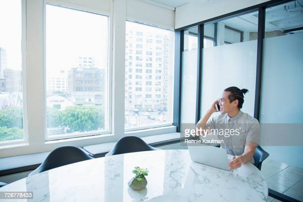 Smiling Chinese businessman talking on cell phone in office