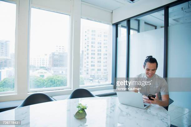Smiling Chinese businessman texting on cell phone in office